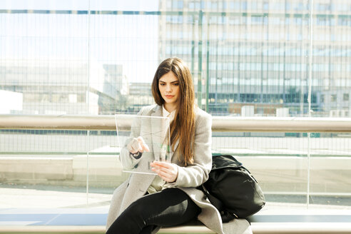 Spain, Barcelona, portrait of young businesswoman using futuristic portable device at station - VABF01597