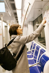Spain, Barcelona, smiling young woman with backpack looking at map in underground train - VABF01600