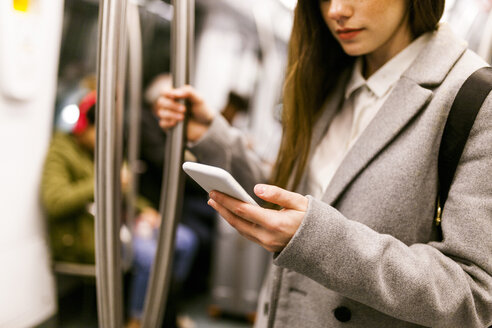 Businesswoman using cell phone in underground train, partial view - VABF01603