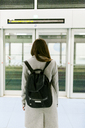Back view of woman with black backpack - VABF01606