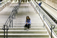 Young woman sitting on stairs using cell phone and earphones - VABF01609