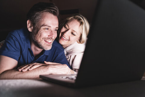 Happy couple lying on couch at home using laptop - UUF13485