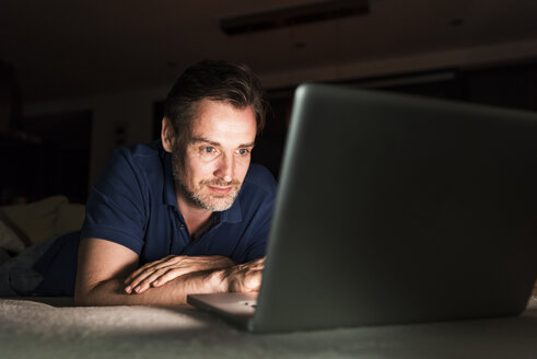 Portrait of man lying on couch at home looking at laptop - UUF13488