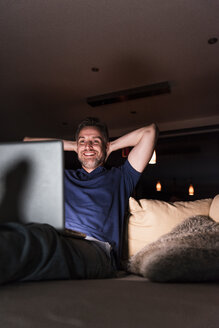 Man sitting on couch at home looking at laptop - UUF13491