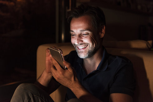 Portrait of happy mature man using cell phone at home - UUF13494