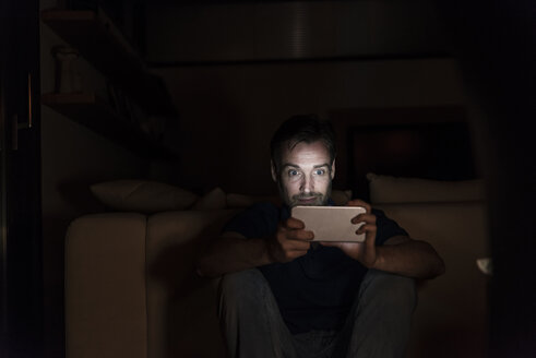 Man sitting in the dark at home starring at smartphone - UUF13497