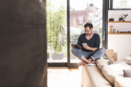Mature man with cup of coffee sitting on backrest of couch using tablet - UUF13500