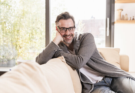 Portrait of smiling man relaxing on couch at home - UUF13503