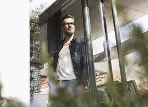 Portrait of confident mature man standing in front of terrace door of his house - UUF13506