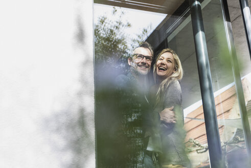 Happy mature couple standing on terrace of their house - UUF13515