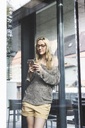 Portrait of blond mature woman standing in front of house looking at smartphone - UUF13518