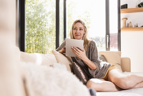 Portrait of mature woman with tablet sitting on couch in the living room - UUF13521