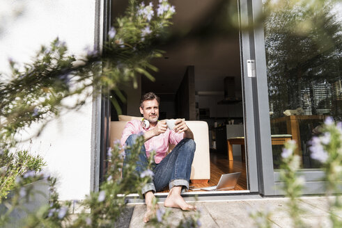 Content man sitting with cup of coffee  at open terrace door - UUF13524
