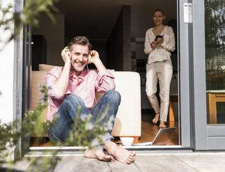 Happy man sitting at open terrace door listening music with headphones - UUF13527