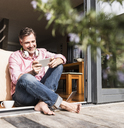 Smiling mature man sitting at open terrace door looking at smartphone - UUF13533