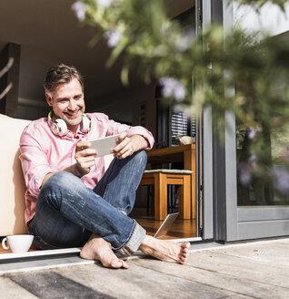 Smiling mature man sitting at open terrace door looking at smartphone - UUF13533