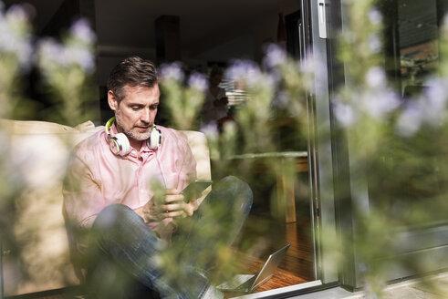 Mature man sitting at open terrace door using smartphone - UUF13536