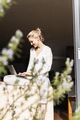 Smiling mature woman sitting at open terrace door using laptop - UUF13539