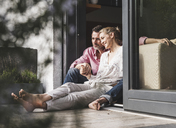 Content mature couple relaxing together at open terrace door - UUF13545