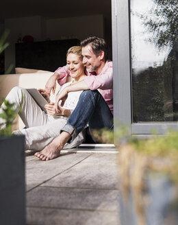 Mature couple relaxing together at open terrace door using tablet - UUF13548