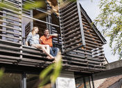 Mature couple relaxing together on balcony of their house - UUF13554