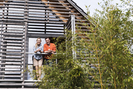 Smiling mature couple standing side by side on balcony of their house - UUF13560
