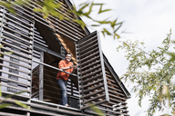 Man with smartphone standing on balcony of his house looking at distance - UUF13563