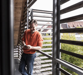 Smiling mature man standing on balcony of his house looking at smartphone - UUF13566