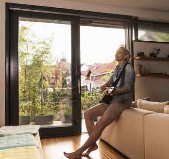 Mature woman singing and playing guitar in the living room - UUF13575