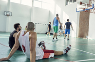 Basketball players during break, sitting on court - ZEDF01355
