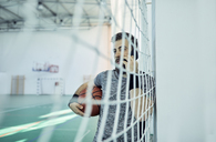 Man with basketball using smartphone behind net, indoor - ZEDF01382