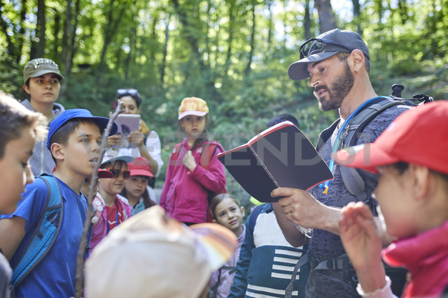 Man reading to kids on a field trip in forest - ZEDF01393