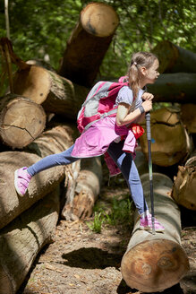 Girl balancing on logs in forest - ZEDF01405