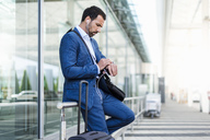 Businessman at airport, looking on watch - DIGF04189
