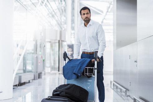 Businessman using baggage cart - DIGF04213