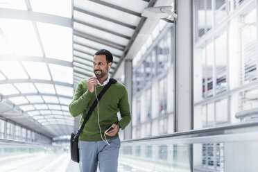 Businessman using smartphone on moving walkway - DIGF04228