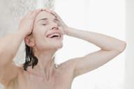 Smiling woman taking shower - CUF01159