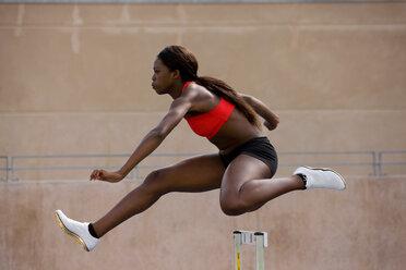 Runner jumping over hurdles on track - CUF01265