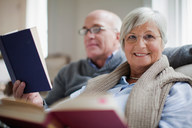 Smiling older couple reading books - CUF01364