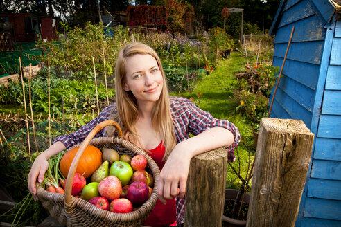 Woman gathering vegetables in garden - CUF01505