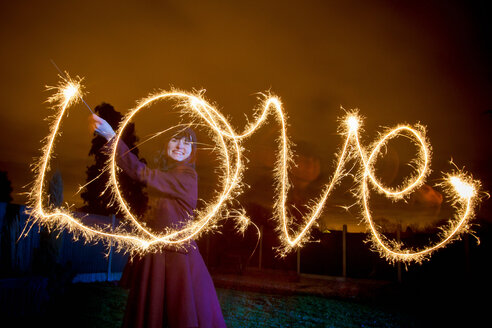 Woman writing LOVE with sparkler - CUF01526