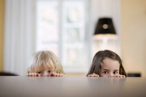 Children looking over table edge - CUF01553