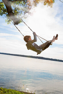 Boy swinging from tree by lake - CUF01610