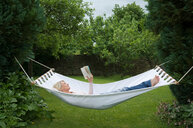 Woman relaxing in hammock in garden - CUF01826