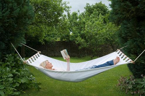 Woman relaxing in hammock in garden - CUF01826