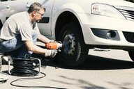 Mature man changing car tire - MAEF12571
