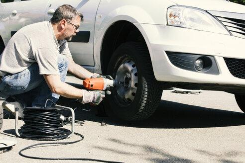 Mature man changing car tire - MAEF12571