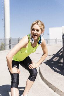 Woman jogging in the city, taking a break - UUF13588