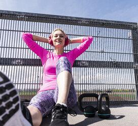Sportive woman wearing headphones, taking a break, listening music - UUF13621