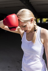 Woman with boxing gloves looking tired - UUF13624